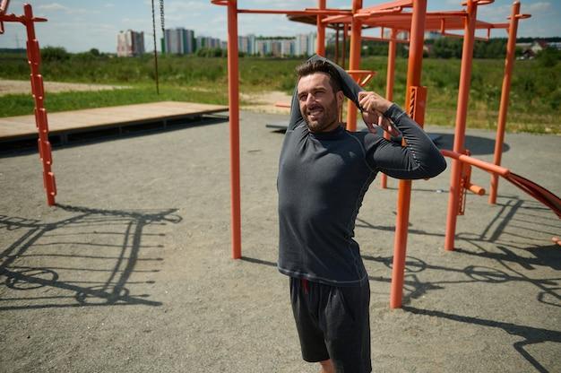 野外でスポーツグラウンドでトレーニングする前に背中の後ろで腕を伸ばしているハンサムな若い大人40歳のヨーロッパのスポーティーな男。美しい晴れた日に屋外でトレーニングを楽しむ成熟したスポーツマン