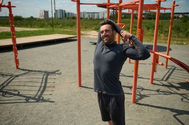 Handsome young adult 40 years old european sporty man stretching arms behind his back before training on the sportsground in open air. mature sportsman enjoying workout outdoor on beautiful sunny day
