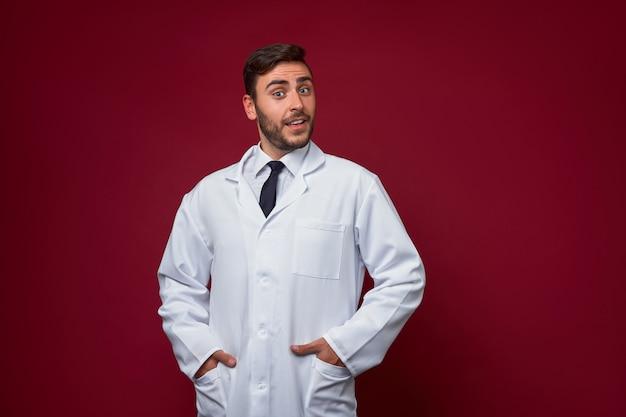 Красивый молодой взрослый кавказский доктор на красной предпосылке. студент-медик