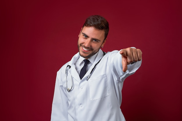 Красивый молодой взрослый кавказский доктор на красной предпосылке