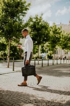 Красивый молодой афро-американский бизнесмен с помощью мобильного телефона на улице