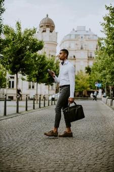 Красивый молодой афро-американский бизнесмен, используя мобильный телефон, управляя улицей