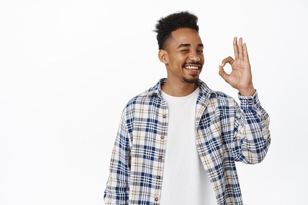 Bel giovane ragazzo afroamericano che sorride soddisfatto, mostra ok, ok segno zero e annuisce in segno di approvazione, valuta cosa buona, loda un lavoro eccellente, consiglia negozio, in piedi su bianco