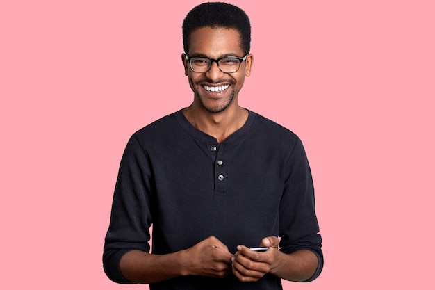 Handsome young african american man holds smart phone with smile, has great news from friend. dark skinned model poses on pink. people and technology concept.