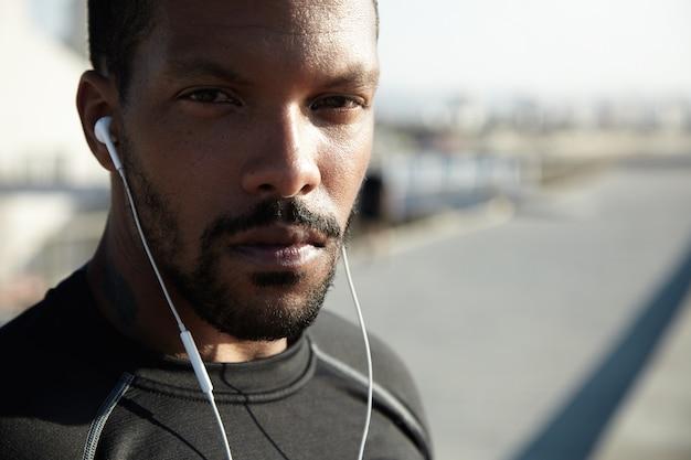 Abiti sportivi d'uso del giovane corridore o pareggiatore afroamericano bello che si esercitano all'aperto di mattina. maschio nero attraente che ascolta la musica motivante per l'addestramento usando le sue cuffie