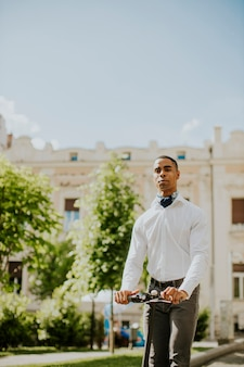 Красивый молодой афроамериканец, использующий электросамокат на улице