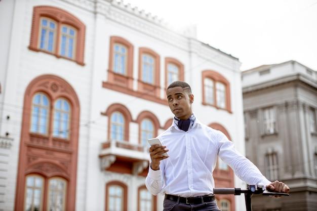 Красивый молодой афроамериканец с помощью мобильного телефона, стоя с электросамокатом на улице