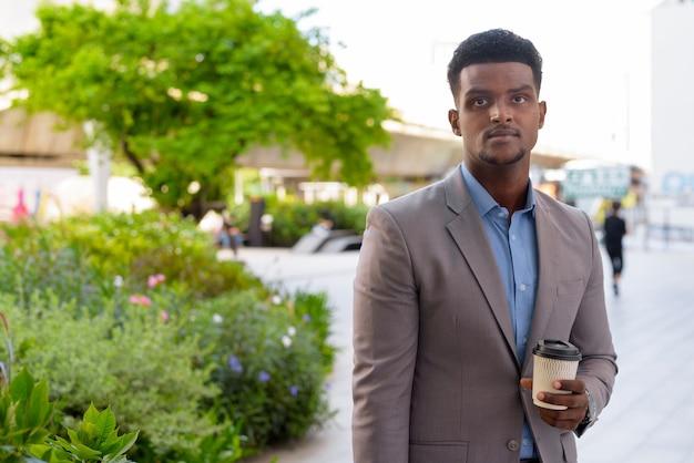 テイクアウトコーヒーのカップを屋外で運ぶハンサムな若いアフリカのビジネスマン