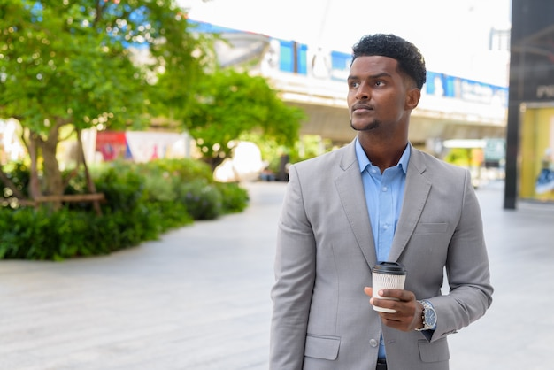 Handsome young african businessman outdoors carrying cup of take away coffee while thinking