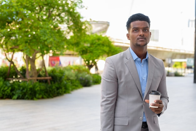 Handsome young african businessman outdoors carrying cup of take away coffee