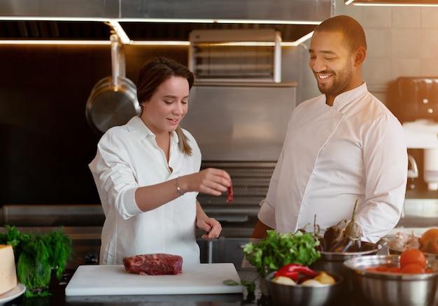 Красивый молодой африканский повар готовит вместе с кавказской подругой на кухне повар учит девушку готовить. мужчина и женщина готовят на профессиональной кухне. межрасовые отношения