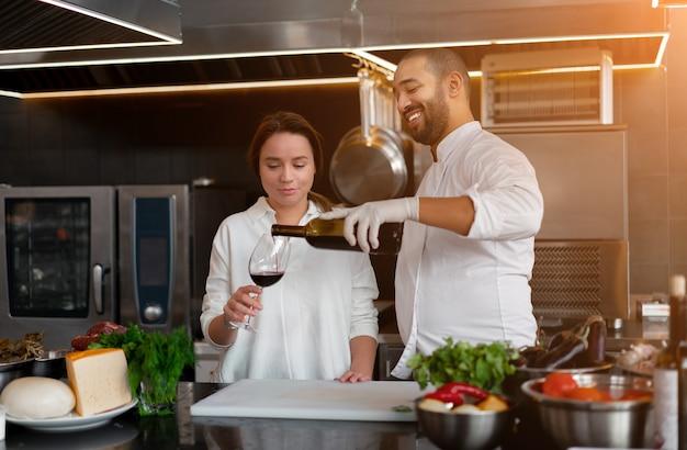 잘 생긴 젊은 아프리카 요리사는 레드 와인 성분을 사용하여 부엌에서 백인 여자 친구와 함께 요리하고 있습니다. 요리사는 소녀에게 요리하는 법을 가르칩니다. 남자와 여자는 전문 부엌에서 요리.