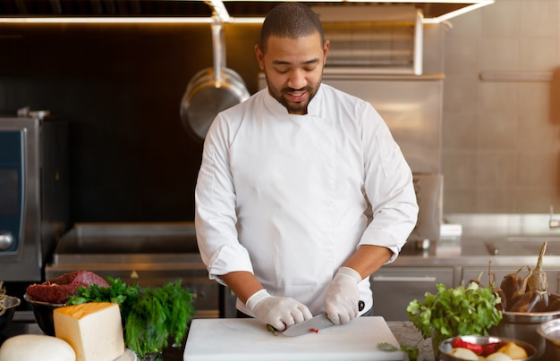고기와 치즈 야채 식사를 준비하는 레스토랑의 전문 주방에 서 있는 잘생긴 젊은 아프리카 요리사. 쿡 제복을 입은 남자의 초상화 금속 칼으로 고추를 잘라냅니다.