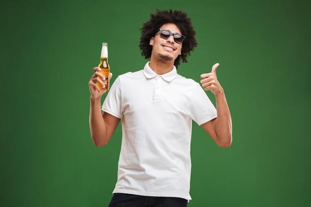 ビールを飲みながらハンサムな若いアフリカ巻き毛男は親指を立てます。