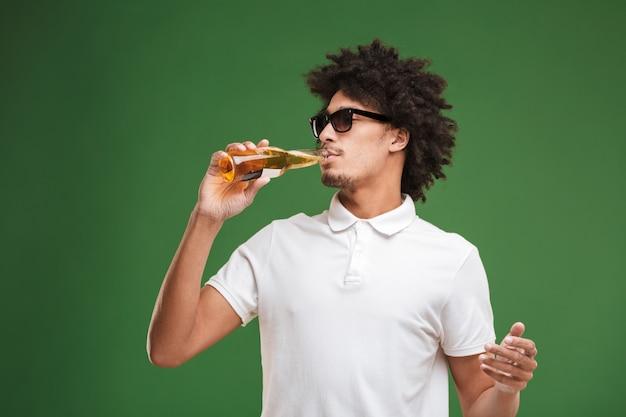 ハンサムな若いアフリカ巻き毛の男がビールを飲みます。