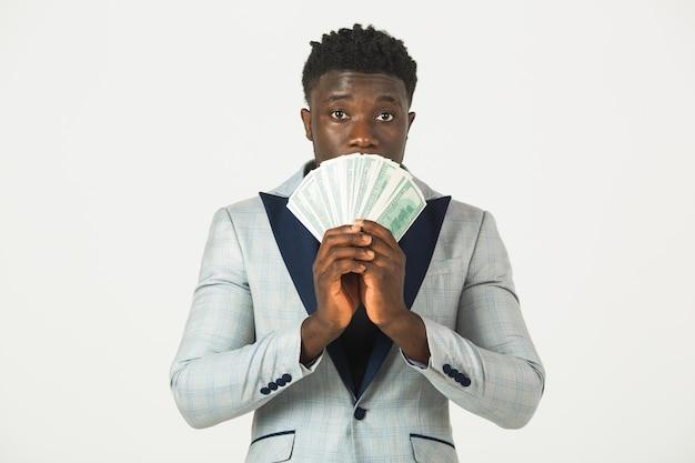 彼の手でドルを持つジャケットでハンサムな若いアフリカ男性