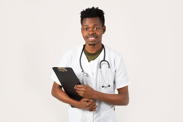 그의 손에 폴더와 의료 가운에 흰색 배경에 잘 생긴 젊은 아프리카 남성