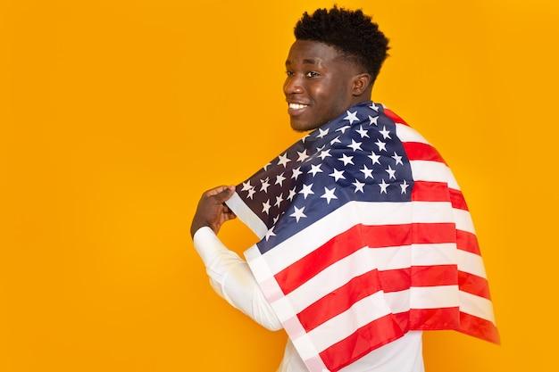 Красивый молодой африканский мужчина с американским флагом на желтом фоне
