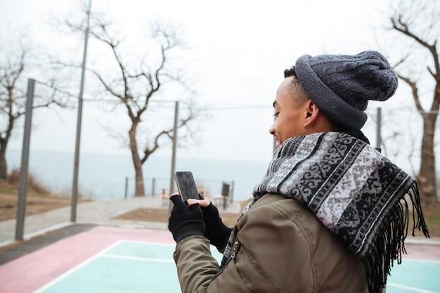 Красивый молодой африканский человек в чате по телефону.