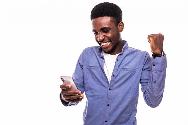 携帯電話を押しながら灰色の壁に立っている間身振りで示すハンサムな若いアフリカ人