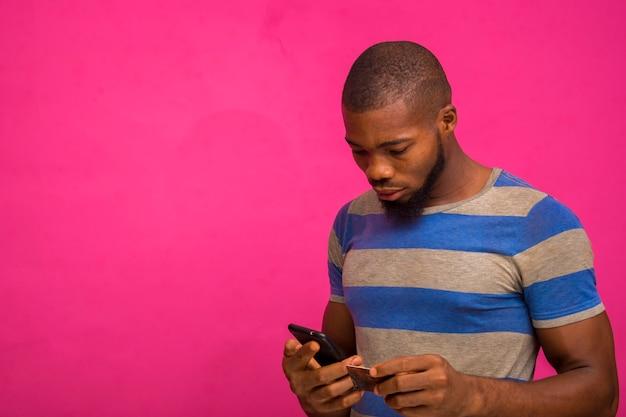 Красивый молодой африканец изолирован на розовом фоне держит свою кредитную карту и смартфон