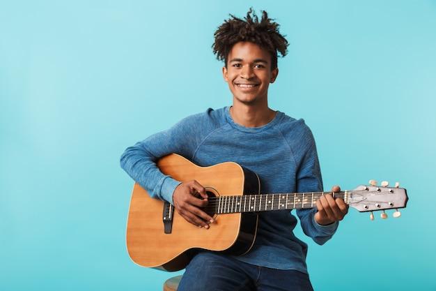 青の上に孤立して座っている間ギターを弾くハンサムな若いアフリカ人