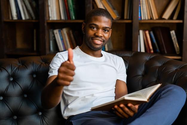 Красивый молодой африканец читает книгу с жестом руки