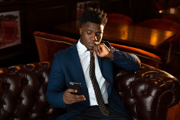Handsome young african man in suit indoors with mobile phone