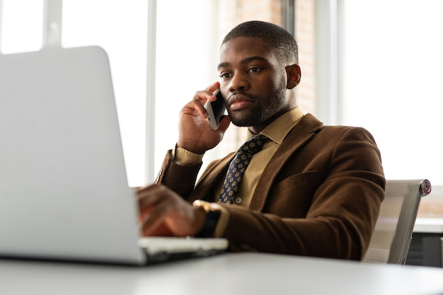 Handsome young african man in suit at table in office with laptop