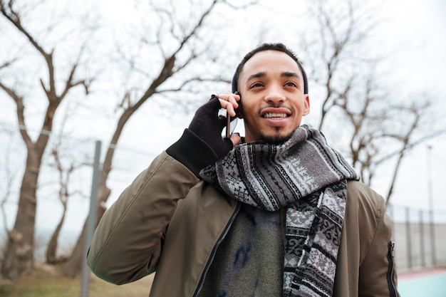 Handsome young african man talking by phone.