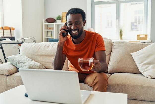 집에서 시간을 보내는 동안 전화로 얘기하고 웃고 잘 생긴 젊은 아프리카 남자