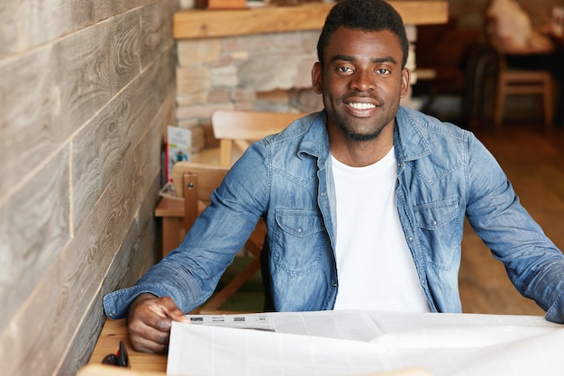 Handsome young african man wearing denim jacket over white t-shirt sitting at cozy cafe, holding newspaper, reading world news