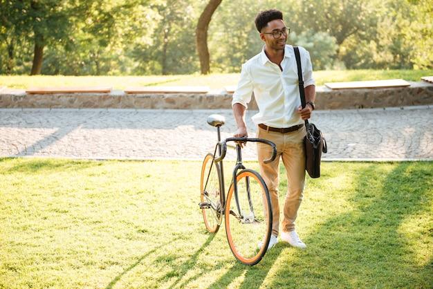 Giovane uomo africano bello con la bicicletta all'aperto