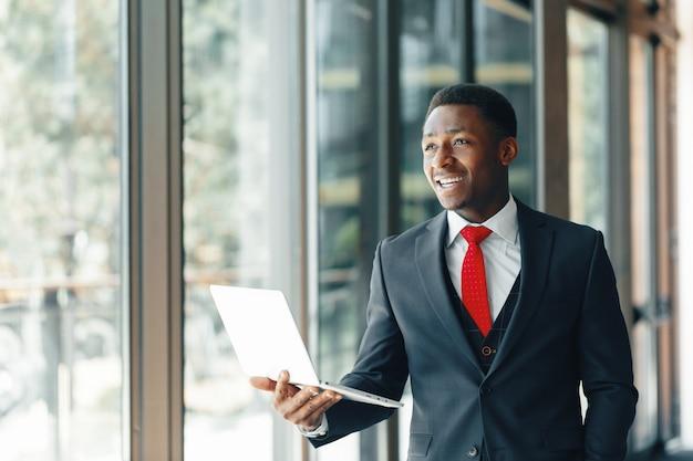 ラップトップを押しながら笑みを浮かべて古典的なスーツでハンサムな若いアフロアメリカ人実業家