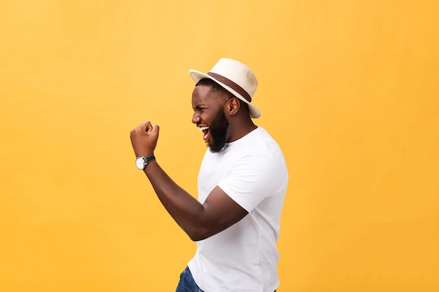 Handsome young afro-american man employee feeling excited, gesturing actively, keeping fists clenched, exclaiming joyfully with mouth wide opened