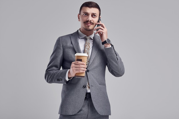 Handsome young arabic businessman with mustache in fashion gray suit
