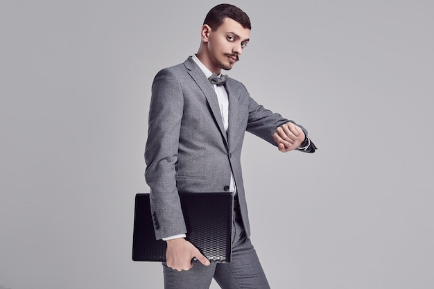 Handsome young arabic businessman with mustache in gray suit holds laptop