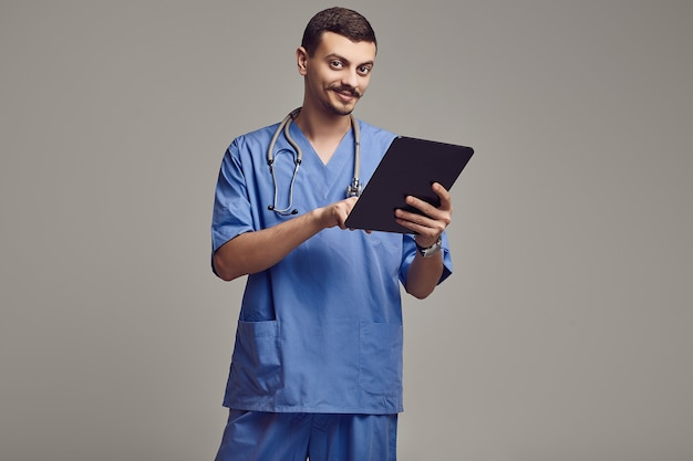 Handsome young arabic doctor with fancy mustache in blue