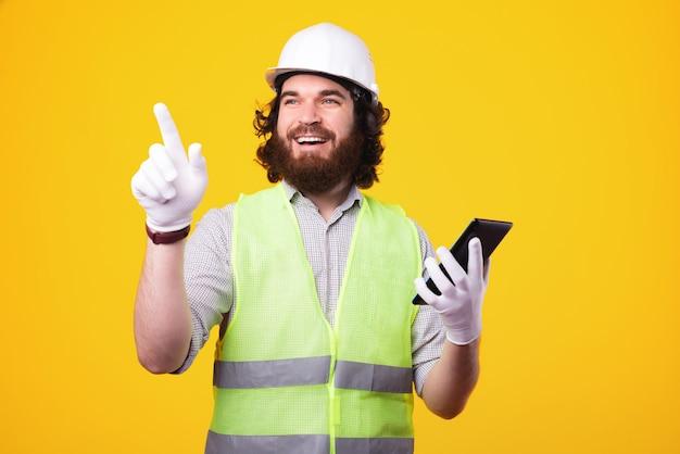 タブレットを保持し、黄色の背景の上に離れて指しているハンサムな若い建築家の男