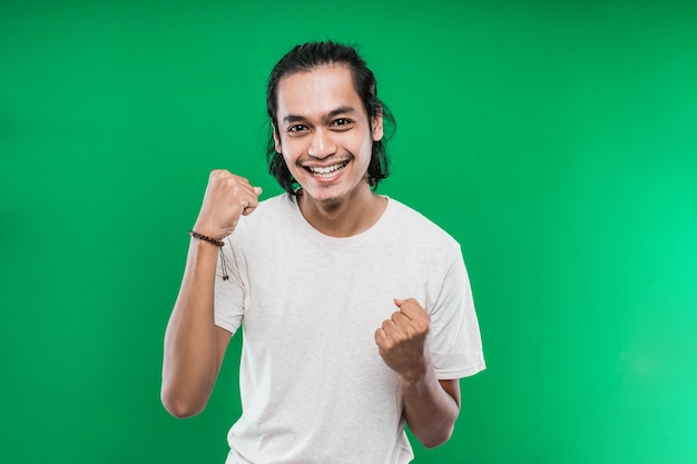 Handsome young asian man expressing happiness with clenched into fists and raised two hands isolated on a green background