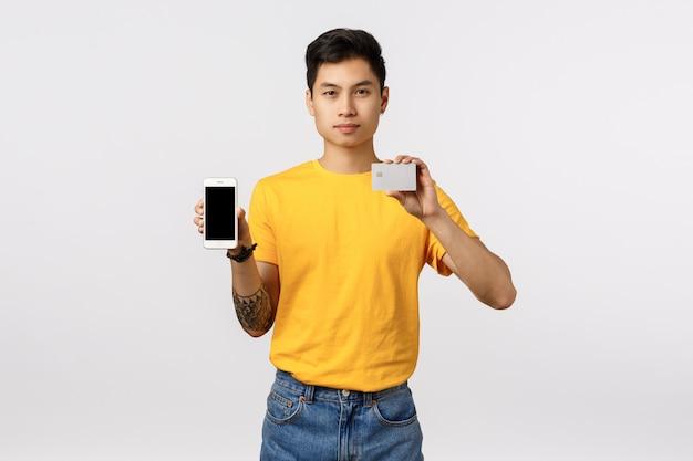 Красивый молодой азиатский человек в желтой футболке держа smartphone и кредитную карточку