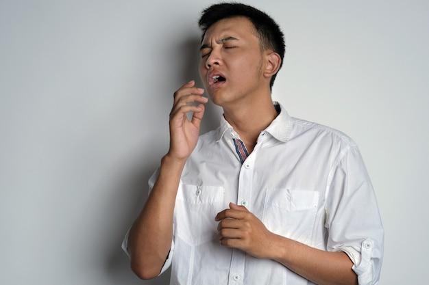 잘 생긴 젊은 아시아 남자가 입을 가리려고 손으로 재채기를 할 것입니다