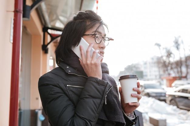 Красивый молодой азиатский человек говоря на телефоне пока выпивающ кофе.