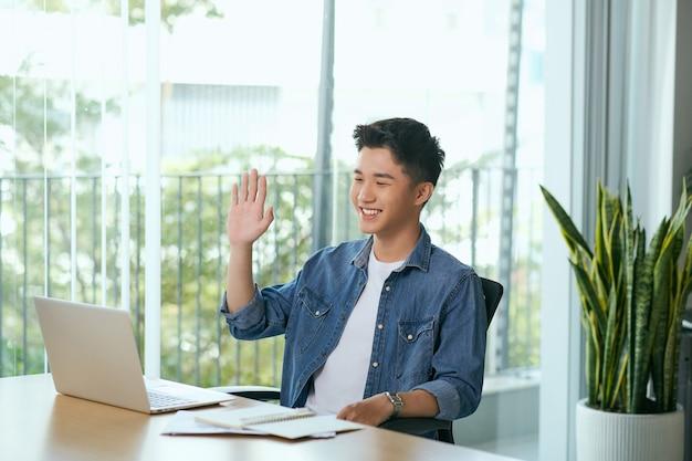 ノートパソコンとタブレットを持ってコーヒーショップで働くハンサムな若いアジア人男性。