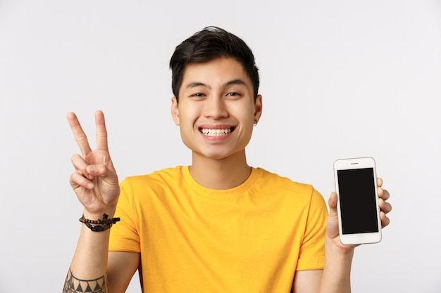 Handsome young asian man in yellow t-shirt holding victory sign and showing victory sign