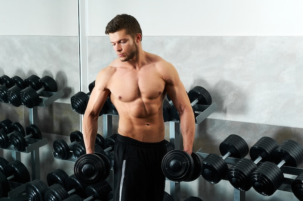 잘 생긴 젊은 선수는 체육관에서 운동을