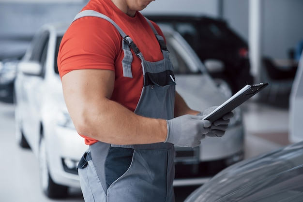 Handsome young auto mechanic in uniform is examining car in auto service
