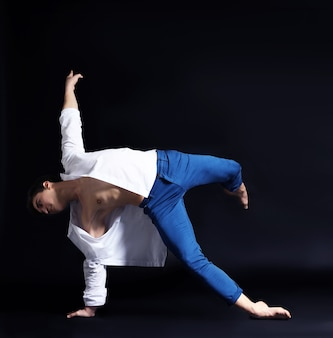 暗い表面のハンサムな若いバレエダンサー
