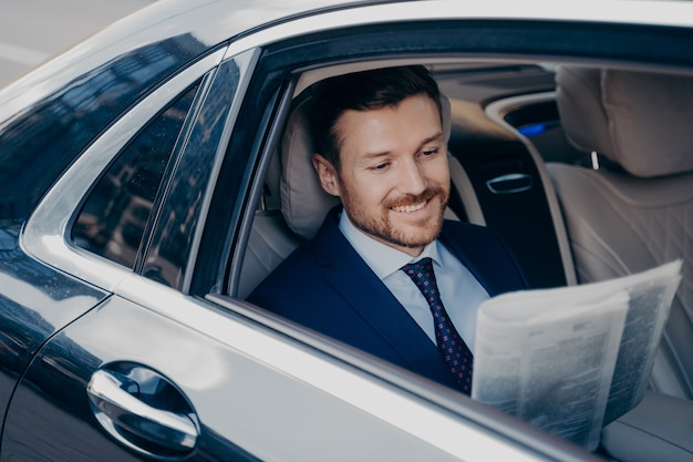 Handsome young banker in smart formal tuxedo suit reads newspaper with smile, while sitting on passenger seat in expensive car, goes to corporate executive meeting in new office