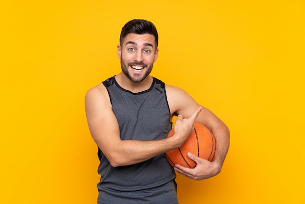 Handsome young basketball player man over isolated white wall pointing to the side to present a product